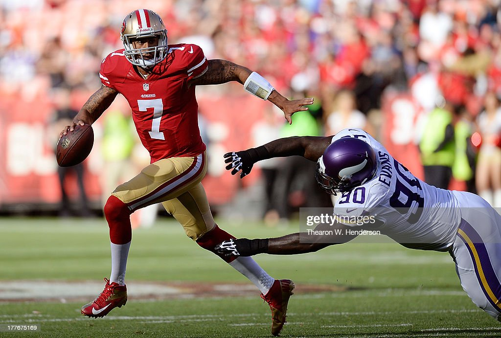 Colin Kaepernick #7 of the San Francisco 49ers scrambles away from the rush of Fred Evans #90 of the Minnesota Vikings in the first quarter at Candlestick Park on August 25, 2013 in San Francisco, California.