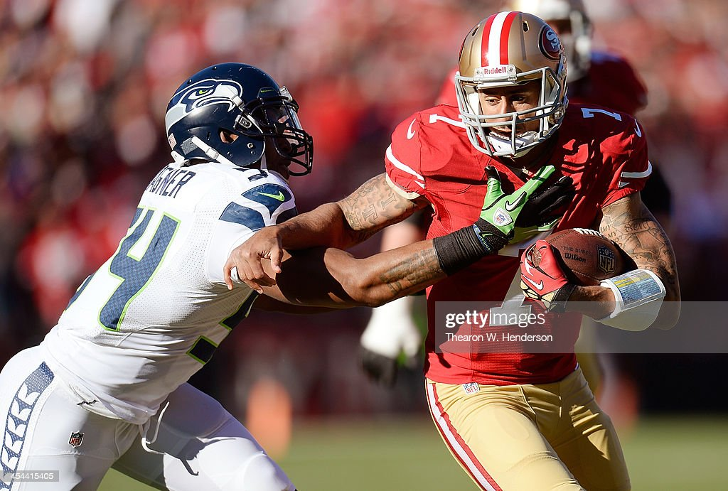 Colin Kaepernick #7 of the San Francisco 49ers scrambling with the ball gets grabbeb by his jersey from Bobby Wagner #54 of the Seattle Seahawks during the first quarter at Candlestick Park on December 8, 2013 in San Francisco, California.