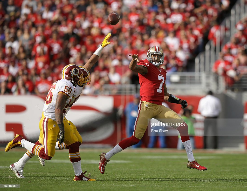 Colin Kaepernick #7 of the San Francisco 49ers shovels a pass over Keenan Robinson #52 of the Washington Redskins and Perry Riley #56 of the Washington Redskins at Levi's Stadium on November 23, 2014 in Santa Clara, California.