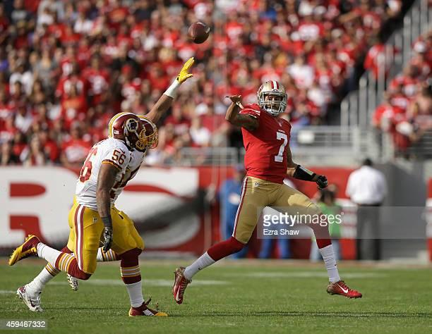 Colin Kaepernick of the San Francisco 49ers shovels a pass over Keenan Robinson of the Washington Redskins and Perry Riley of the Washington Redskins...
