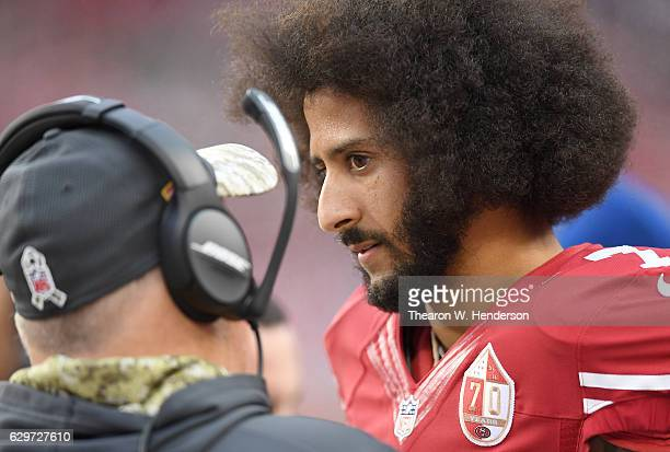 Colin Kaepernick of the San Francisco 49ers talks with head coach Chip Kelly on the sidelines during the fourth quarter of their NFL football game...