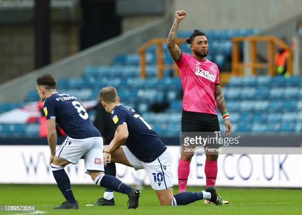 Colin Kazim-Richards of Derby County raises his right fist as other players take the knee ahead of the Sky Bet Championship match between Millwall...