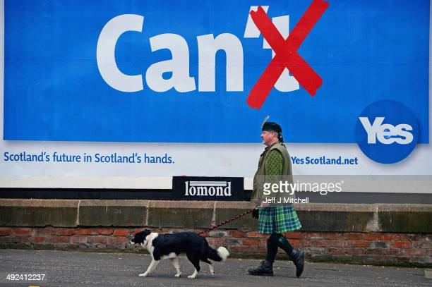 Colin MacDonald Provan walks his dog Colleen down Glasgow High Street past a Yes referendum campaign billboard On May 20 2014 in Glasgow Scotland A...