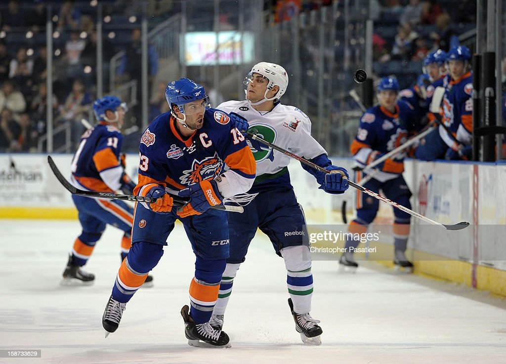 Colin McDonald #13 of the Bridgeport Sound Tigers reaches for the puck against Ryan Bourque # 9 of the Connecticut Whale during an American Hockey League game on December 26, 2012 at the Webster Bank Arena at Harbor Yard in Bridgeport, Connecticut.