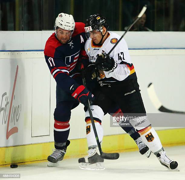 Colin McDonald of USA is challenged by Yasin Ehliz of Germany during the international ice hockey friendly match between Germany and USA at Arena...