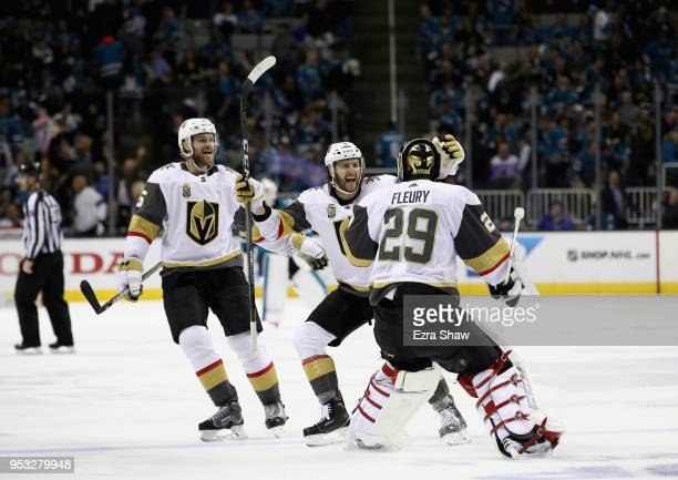 Colin Miller and Jon Merrill congratulate MarcAndre Fleury of the Vegas Golden Knights after they beat the San Jose Sharks in Game Three of the...