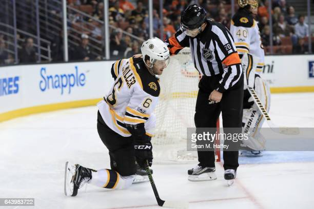 Colin Miller of the Boston Bruins gets up from the ice after being hit as referee Tim Peel helps him up during the third period of a game against the...