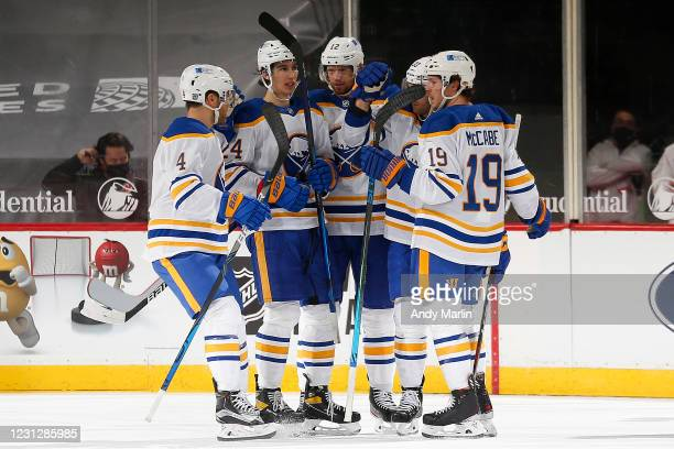 Colin Miller of the Buffalo Sabres is congratulated by his teammates after scoring a goal against the New Jersey Devils during the first period at...