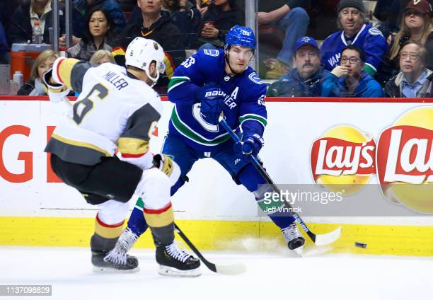 Colin Miller of the Vegas Golden Knights looks on as Bo Horvat of the Vancouver Canucks passes the puck up ice during their NHL game at Rogers Arena...