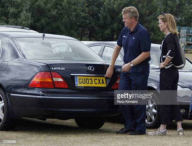 Colin Montgomerie of Scotland and his wife open the trunk of his car after withdrawing from the Championships through injury during the first round...