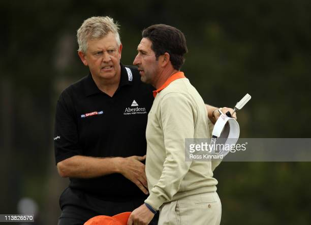 Colin Montgomerie of Scotland and Jose Maria Olazabal of Spain on the 18th green following news of the death of Seve Ballesteros during the third...
