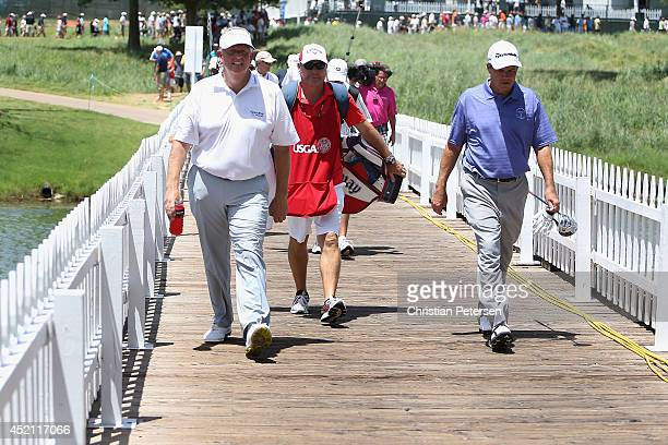 Colin Montgomerie of Scotland and Scott Dunlap cross a bridge as the walk up the ninth hole during the final round of the 2014 US Senior Open...