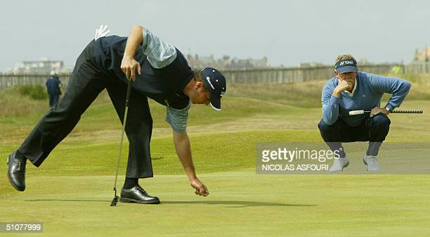 Colin Montgomerie of Scotland contemplates a putt as Mike Weir of Canada removes debris from the 1st green during the third round of the 133rd Open...