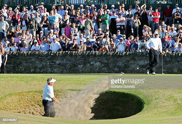 Colin Montgomerie of Scotland hits out of the Road Hole bunker on the 17th green as Tiger Woods of the US watches during the third round of the 134th...