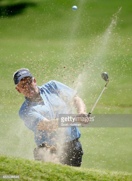 Colin Montgomerie of Scotland plays a bunker shot on the third hole during the second round of the 2014 US Senior Open Championship at Oak Tree...