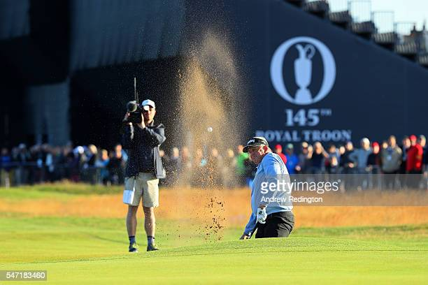 Colin Montgomerie of Scotland plays a shot from a bunker on the 1st hole during the first round on day one of the 145th Open Championship at Royal...
