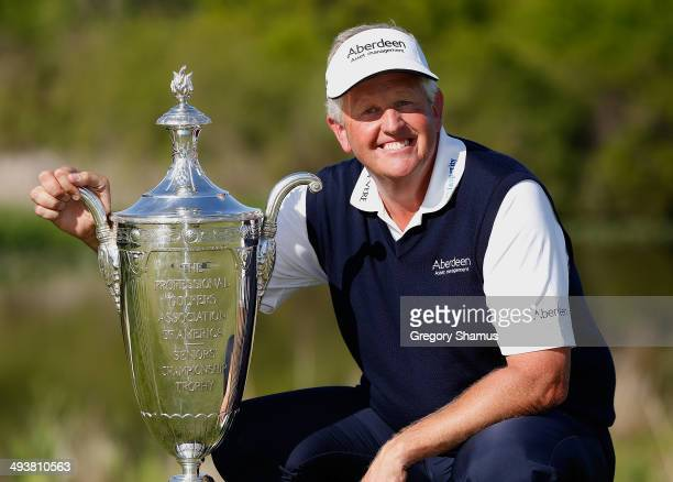 Colin Montgomerie of Scotland poses with the Alfred S Bourne Trophy after winning the 2014 Senior PGA Championship presented by KitchenAid with a...