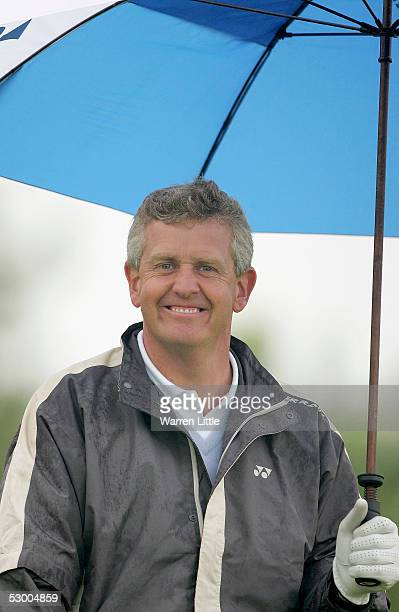 Colin Montgomerie of Scotland smiles as he shelters from the rain on the second hole during the proam event before The Celtic Manor Wales Open 2005...
