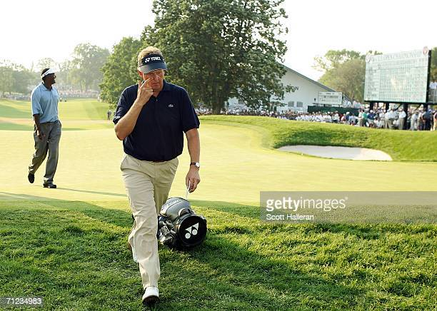 Colin Montgomerie of Scotland walks off the 18th green with Vijay Singh of Fiji after the final round of the 2006 US Open Championship at Winged Foot...