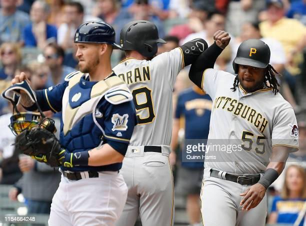 Colin Moran of the Pittsburgh Pirates and Josh Bell of the Pittsburgh Pirates celebrate the home run in front of Yasmani Grandal of the Milwaukee...