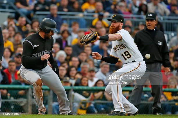 Colin Moran of the Pittsburgh Pirates misses the ball during a run down against Daniel Murphy of the Colorado Rockies in the second inning at PNC...