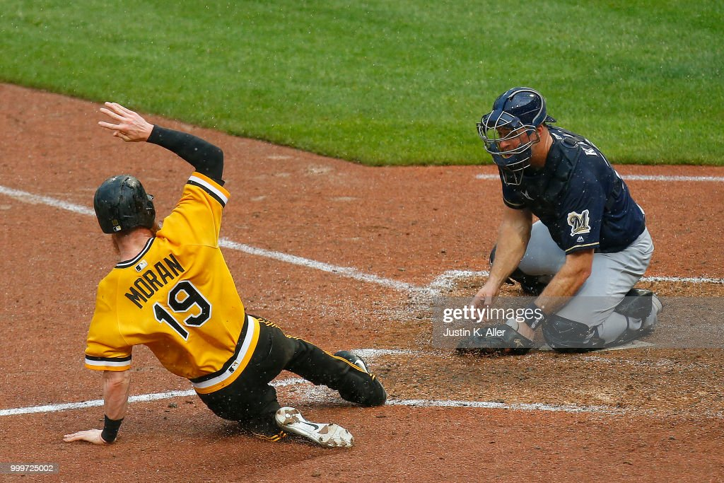 Colin Moran #19 of the Pittsburgh Pirates slides in safe on a two RBI double in the nineteenth inning against Erik Kratz #15 of the Milwaukee Brewers at PNC Park on July 15, 2018 in Pittsburgh, Pennsylvania.