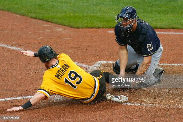 Colin Moran of the Pittsburgh Pirates slides in safe on a two RBI double in the nineteenth inning against Erik Kratz of the Milwaukee Brewers at PNC...