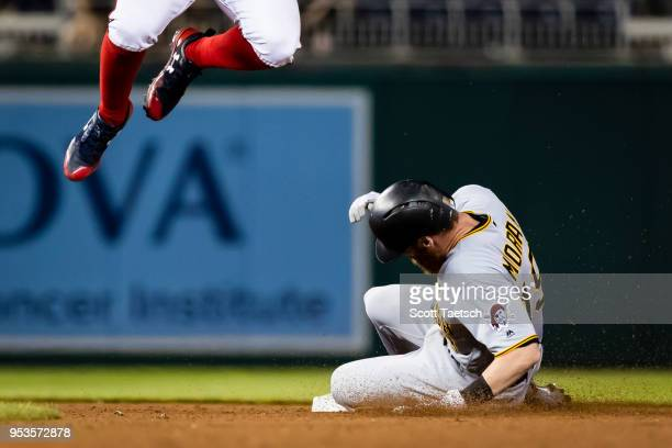 Colin Moran of the Pittsburgh Pirates slides safe into second as Wilmer Difo of the Washington Nationals leaps for the ball during the ninth inning...