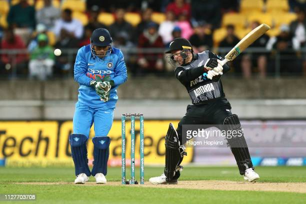 Colin Munro of New Zealand bats while MS Dhoni of India looks on during game one of the International T20 Series between the New Zealand Black Caps...