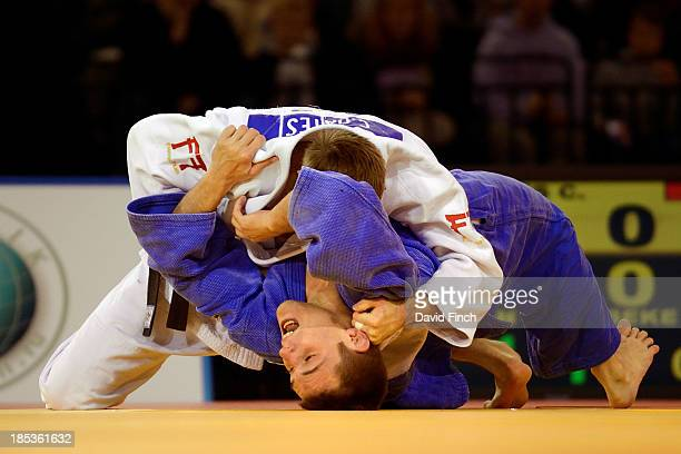 Colin Oates of Great Britain holds a struggling Kenneth Van Gansbeke of Belgium for ippon on his way to the u66kg gold medal during the Glasgow...