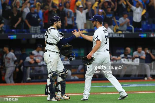 Colin Poche of the Tampa Bay Rays celebrates with Travis d'Arnaud after defeating the Houston Astros 10-3 in Game Three of the American League...