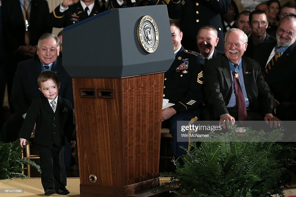Colin Romesha, the son of Medal of Honor recipient Clinton Romesha, peeks around the corner of U.S. President Barack Obama's lectern before a presentation ceremony at the White House February 11, 2013 in Washington, DC. Romesha received the Medal of Honor for actions during combat operations against an armed enemy at Combat Outpost Keating, Kamdesh District, Nuristan Province, Afghanistan on October 3, 2009.