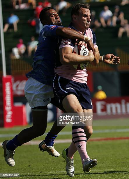 Colin Shaw of Scotland is tackled by Tom Iosefo of Samoa during their rugby match on the first day of the Dubai leg of IRB's Sevens World Series on...