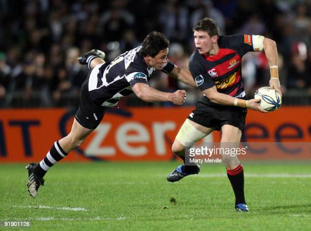 Colin Slade of Canterbury gets tackled by Zac Guildford of Hawks Bay during the Air New Zealand Cup match between the Hawkes Bay Magpies and...
