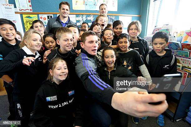 Colin Slade of the All Blacks takes a selfie with students during the All Black To The Nation visit to Mataura school on September 3 2015 in Mataura...
