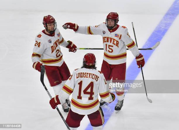 Colin Staub Jarid Lukosevicius and Ian Mitchell of the Denver Pioneers celebrate after Staub scored an empty net goal in the third period against the...