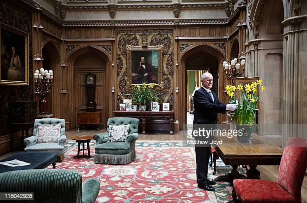 Colin the butler tends to some flowers in the saloon at Highclere Castle on March 15, 2011 in Newbury, England. Highclere Castle has been the...