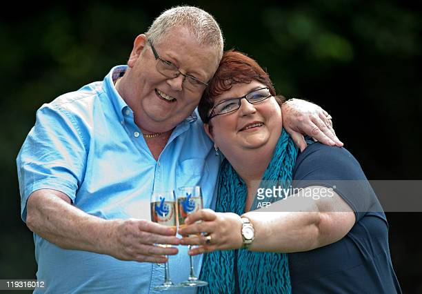 Colin Weir and his wife Chris pose for pictures with champagne during a photocall in Falkirk Scotland on July 15 after winning a record GBP161m in...