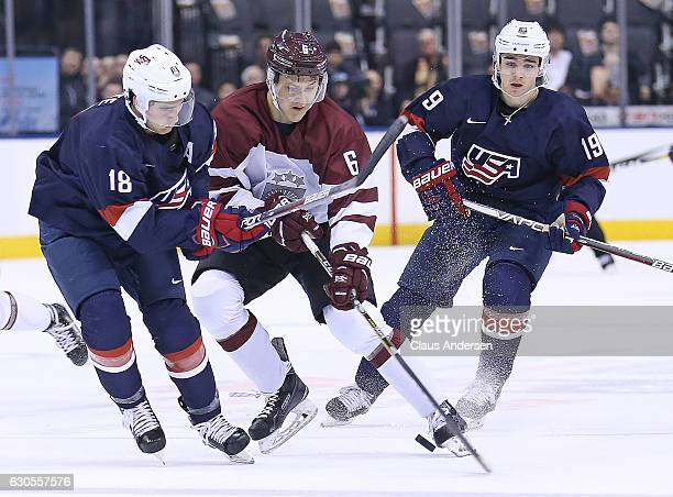 Colin White and Clayton Keller of Team USA skate against Eduards Tralmaks of Team Latvia during a 2017 IIHF World Junior Hockey Championship game at...