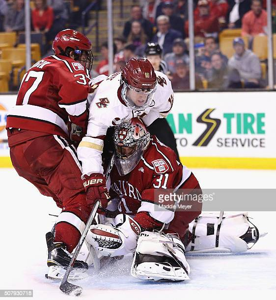 Colin White of the Boston College Eagles collides with Merrick Madsen of the Harvard Crimson while being defended by Desmond Bergin of the Harvard...