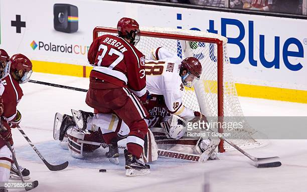 Colin White of the Boston College Eagles is checked by Desmond Bergin of the Harvard Crimson into goalie Merrick Madsen during NCAA hockey in the...