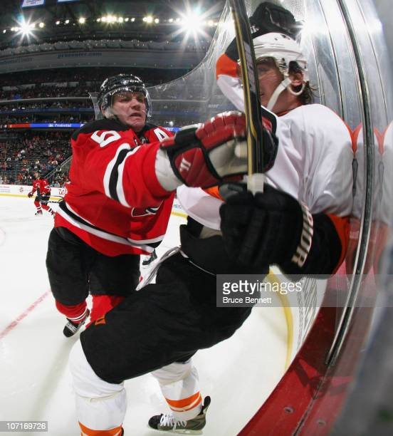 Colin White of the New Jersey Devils hits Nikolay Zherdev of the Philadelphia Flyers at the Prudential Center on November 27 2010 in Newark New Jersey