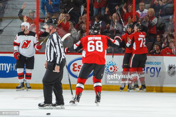 Colin White of the Ottawa Senators celebrates his first NHL goal with teammate Thomas Chabot and Mike Hoffman against the New Jersey Devils at...