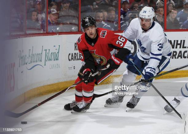 Colin White of the Ottawa Senators controls the puck against Auston Matthews of the Toronto Maple Leafs at Canadian Tire Centre on March 30 2019 in...