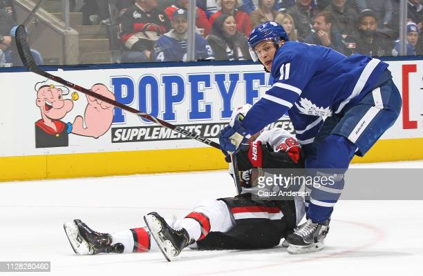 Colin White of the Ottawa Senators is knocked down by Zach Hyman of the Toronto Maple Leafs during an NHL game at Scotiabank Arena on February 6 2019...