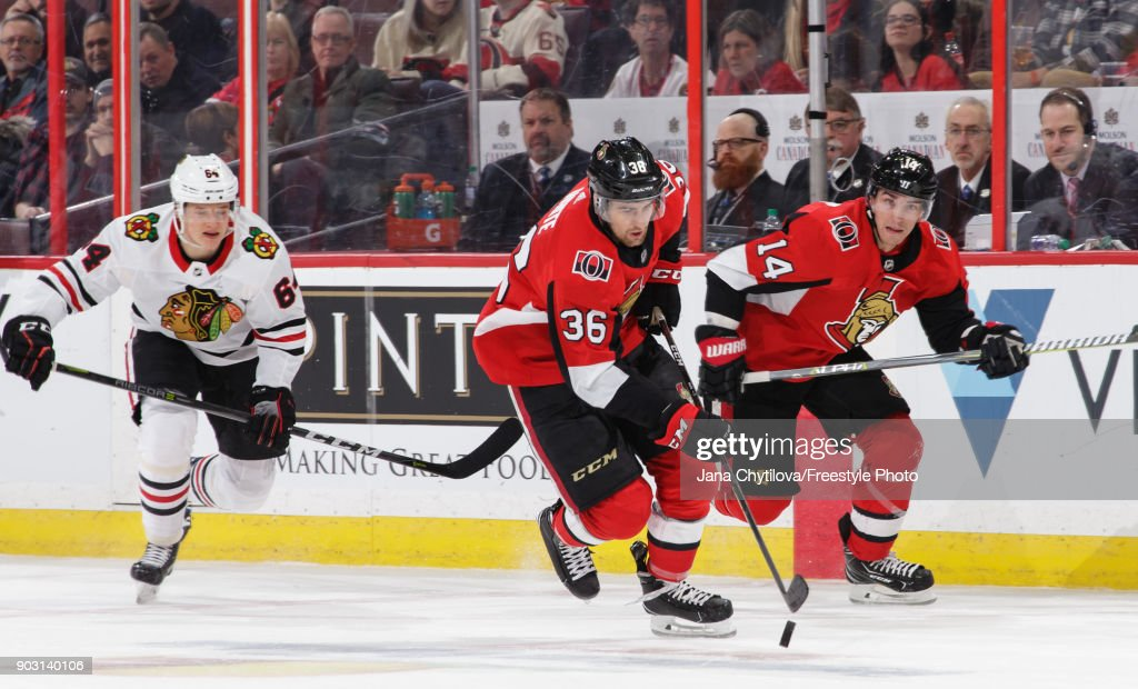 Colin White #36 of the Ottawa Senators skates with the puck with teammate Alexandre Burrows #14 as David Kampf #64 of the Chicago Blackhawks chases them in the second period at Canadian Tire Centre on January 9, 2018 in Ottawa, Ontario, Canada.