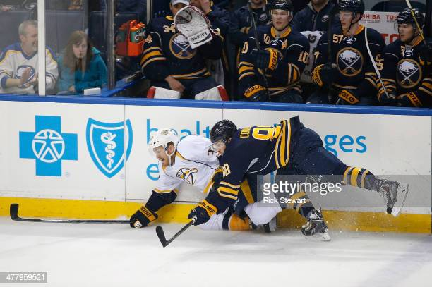 Colin Wilson of the Nashville Predators and Cory Conacher of the Buffalo Sabres fall to the ice at First Niagara Center on March 11 2014 in Buffalo...