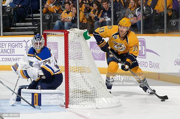Colin Wilson of the Nashville Predators carries the puck behind the net of goalie Jake Allen of the St Louis Bluese during the first period at...