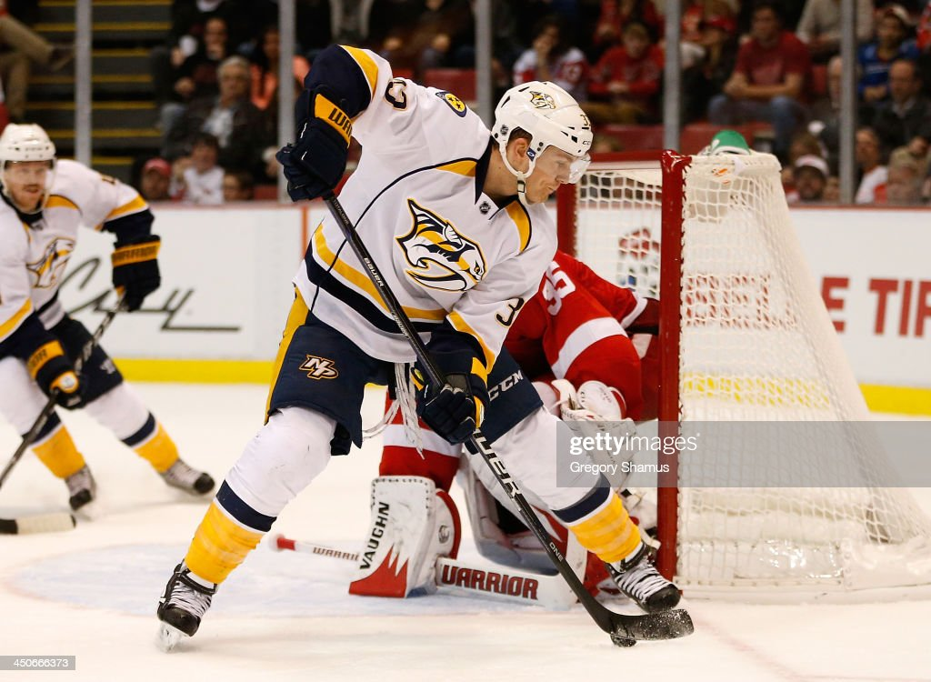Colin Wilson #33 of the Nashville Predators looks to shoot between his legs against goalie Jimmy Howard #35 of the Detroit Red Wings during the third period at Joe Louis Arena on November 19, 2013 in Detroit, Michigan. Nashville won the game 2-0.