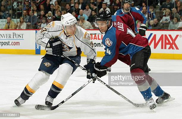 Colin Wilson of the Nashville Predators pressures the goal as JohnMichael Liles of the Colorado Avalanche defends at the Pepsi Center on March 31...